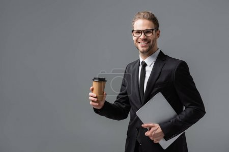 Photo for Happy businessman with takeaway drink and laptop smiling at camera isolated on grey - Royalty Free Image