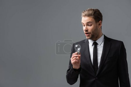 amazed manager in suit holding light bulb isolated on grey