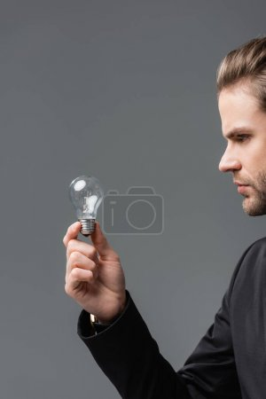 young businessman holding light bulb isolated on grey