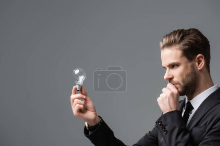 thinking businessman holding hand near face while looking at light bulb isolated on grey