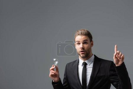 Photo pour Homme d'affaires excité montrant geste idée tout en tenant ampoule isolée sur gris - image libre de droit