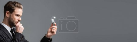 thoughtful businessman looking at light bulb isolated on grey, banner