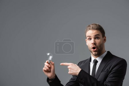 astonished manager pointing at light bulb while looking at camera isolated on grey