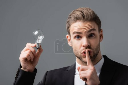 Photo for Thrilled businessman holding light bulb while showing secret gesture isolated on grey - Royalty Free Image