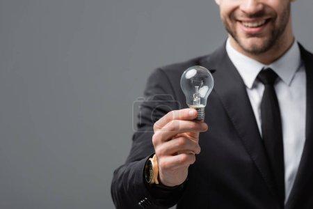 abgeschnittene Ansicht eines lächelnden Geschäftsmannes, der Glühbirne auf verschwommenem Hintergrund zeigt, isoliert auf grau