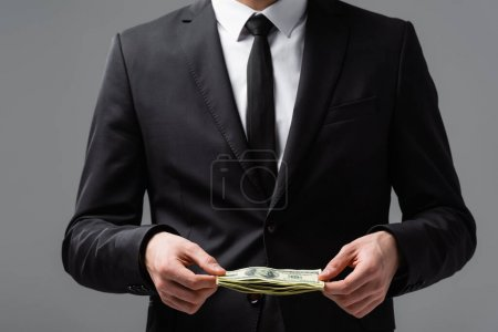 partial view of businessman in formal wear holding dollars isolated on grey