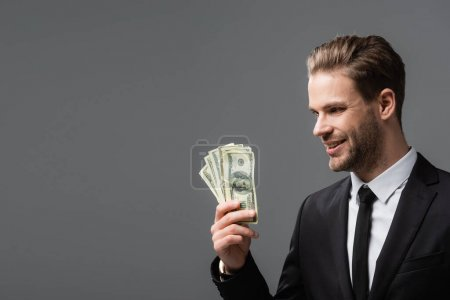 pleased executive manager holding dollars isolated on grey