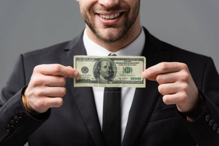 cropped view of smiling businessman holding dollar banknote isolated on grey, blurred background