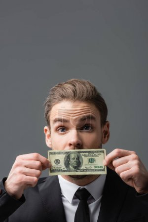 excited businessman covering mouth with dollar banknote isolated on grey