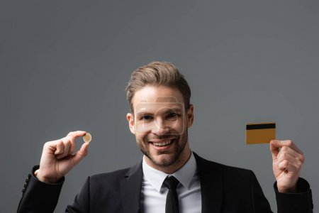 cheerful businessman holding coin and credit card isolated on grey
