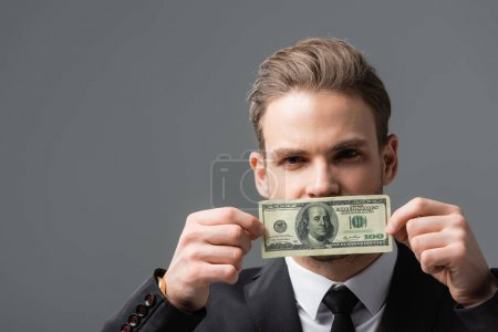 young businessman covering mouth with dollar banknote isolated on grey