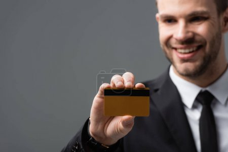 Photo for Happy businessman showing credit card on blurred background isolated on grey - Royalty Free Image