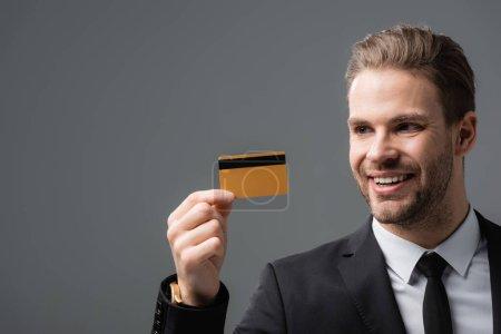 Photo pour Homme d'affaires souriant tenant la carte de crédit isolé sur gris - image libre de droit