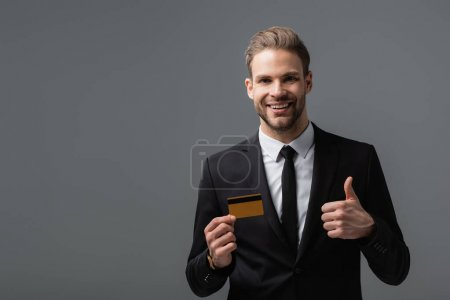 Photo for Pleased manager showing thumb up while holding credit card isolated on grey - Royalty Free Image