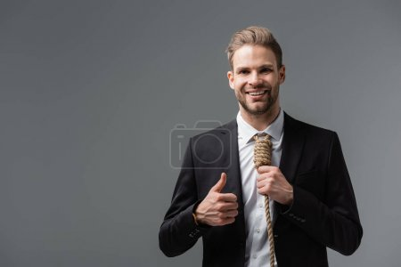 happy businessman with rope instead of tie showing thumb up isolated on grey
