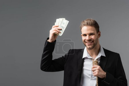cheerful businessman with rope instead of tie holding dollars isolated on grey
