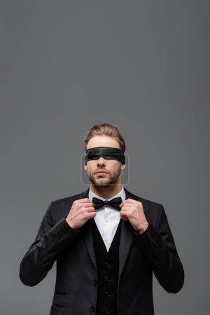 Photo pour Homme d'affaires les yeux bandés ajustant noeud papillon isolé sur gris - image libre de droit