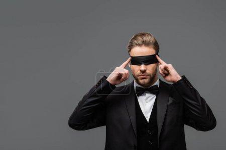 Photo pour Élégant homme d'affaires ajustant bandeau isolé sur gris - image libre de droit