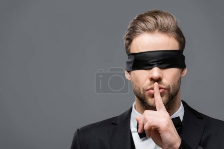 businessman in blindfold showing hush sign isolated on grey