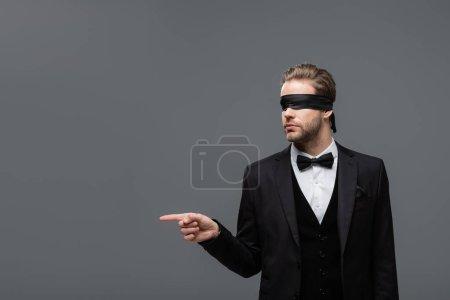 Photo pour Homme d'affaires les yeux bandés en costume noir pointant du doigt isolé sur gris - image libre de droit