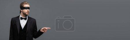 Photo pour Élégant, les yeux bandés homme d'affaires pointant du doigt isolé sur gris, bannière - image libre de droit