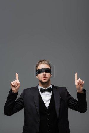 Photo pour Jeune, les yeux bandés homme d'affaires pointant vers le haut avec les doigts isolés sur gris - image libre de droit