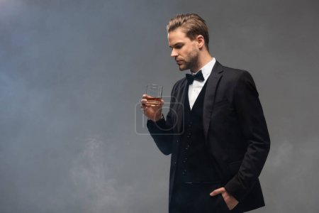young businessman holding whiskey while standing with hand in pocket on grey background with smoke