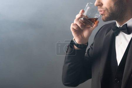 Photo pour Vue partielle de l'homme d'affaires élégant buvant du whisky sur fond gris avec de la fumée - image libre de droit