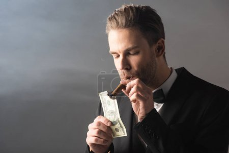 young businessman lighting cigar with hundred dollar banknote on grey background with smoke