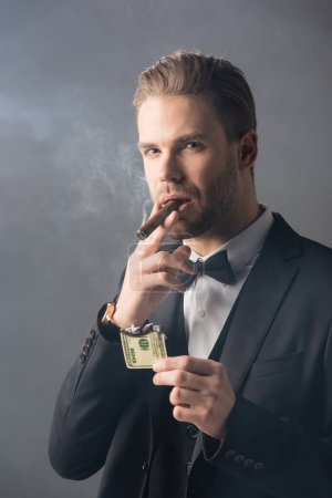 Photo for Rich businessman smoking cigar while holding burned dollar banknote on grey background with smoke - Royalty Free Image