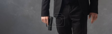 partial view of businessman in black suit holding weapon on grey background with smoke, banner