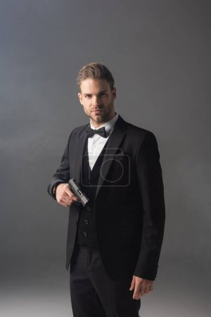 confident businessman looking at camera while standing with gun on grey background with smoke