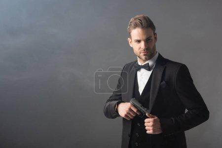 confident businessman hiding gun under blazer on grey background with smoke