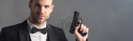 serious businessman looking at camera while holding gun on grey background with smoke, banner
