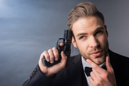 thoughtful businessman touching face while holding gun near head on grey background with smoke