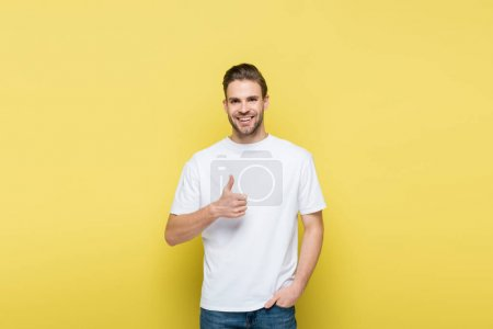 smiling man with hand in pocket showing like on yellow