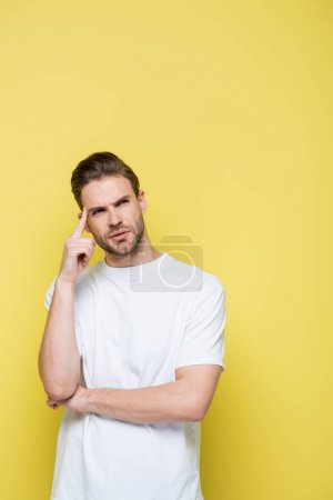thoughtful man looking away and touching head on yellow