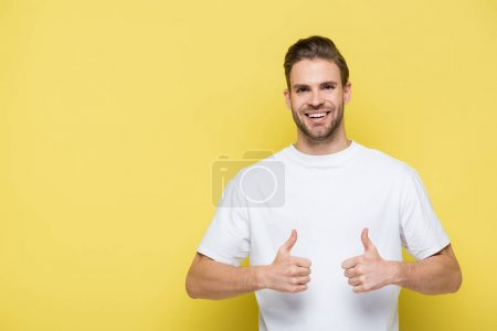 pleased man smiling at camera and showing thumbs up on yellow