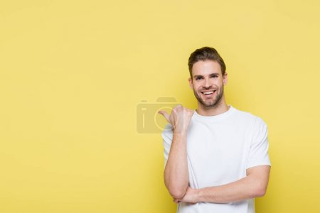 joyful man smiling at camera while pointing with thumb on yellow