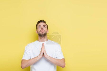 Photo pour Jeune homme levant les yeux tout en montrant un geste d'espoir sur jaune - image libre de droit
