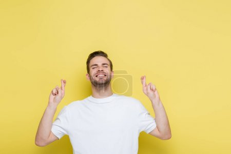 cheerful man with closed eyes standing with crossed fingers on yellow