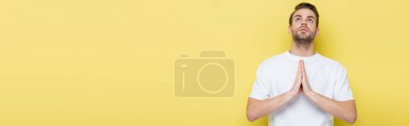 Photo pour Jeune homme levant les yeux en priant sur jaune, bannière - image libre de droit