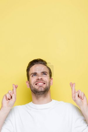 positive man holding crossed fingers while looking up on yellow