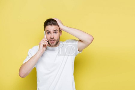 shocked man touching head during conversation on cellphone on yellow