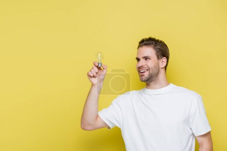 cheerful man looking at light bulb on yellow