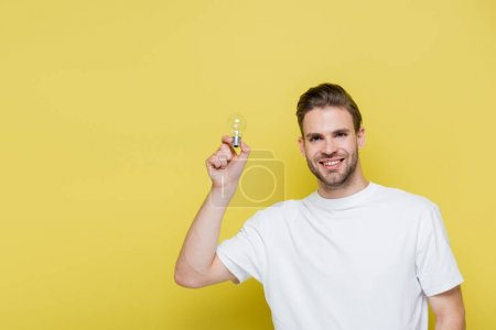 joyful man holding light bulb while smiling at camera on yellow