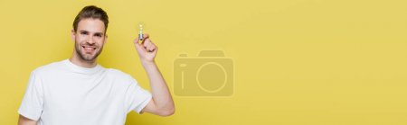 pleased man looking at camera while holding light bulb on yellow, banner