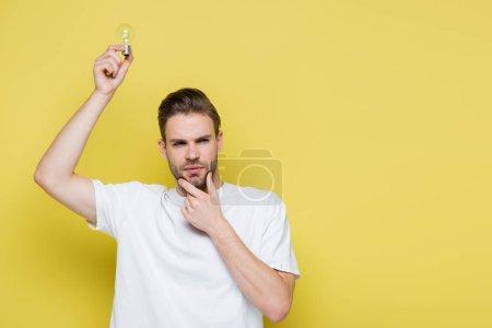 nachdenklicher Mann berührt Kinn, während er Glühbirne in erhobener Hand auf gelb hält