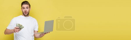 amazed man looking at camera while holding laptop and money on yellow, banner