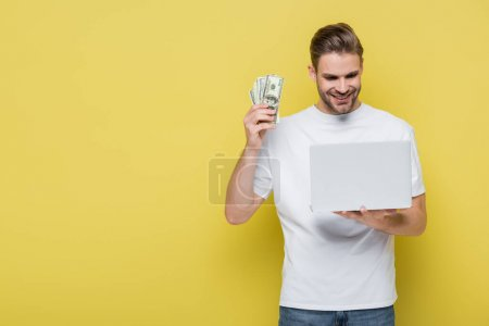 pleased man holding dollar banknotes while looking at laptop on yellow